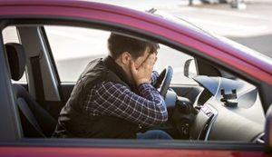 portrait of shocked male driver closing face with hands