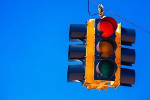 A red traffic signal with a sky blue background | Red Lights and Car Accidents