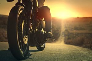 On a roaring motorcycle at sunset | When Poor Road Conditions Cause a Motorcycle Accident