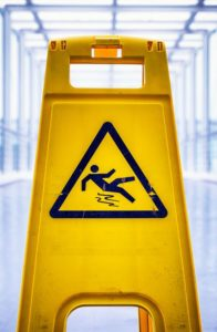 caution wet floor sign at a corridor | How Do Slip and Fall Warning Signs Affect Liability?