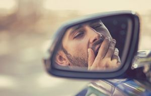 Side mirror view sleepy tired yawning man driving car | Does Driver Fatigue Make You More Likely to be in an Accident