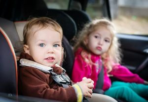 cute small children in car seats in the car