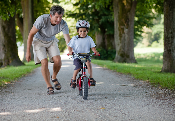 dad helping son ride a bike