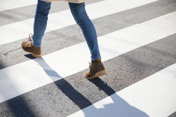 feet of a woman walking in a crosswalk