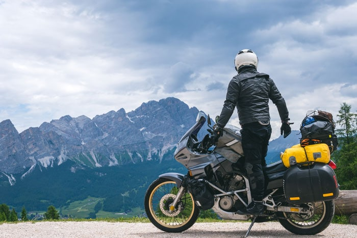 person standing on a parked motorcycle looking at mountains