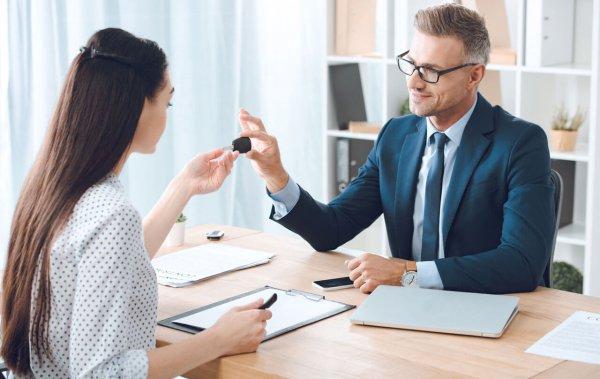 business man handing a woman a car key during a meeting