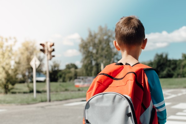 school boy with backpack crossing the street